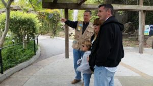 Volunteer Paul Kremser pointing out gibbon behavior to zoo visitors.
