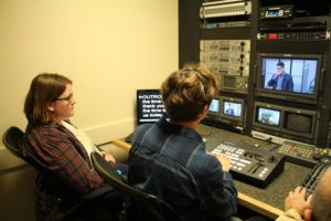 Grace Johnson-Glick and Ethan Messecar working in the control room at CAPS Media.