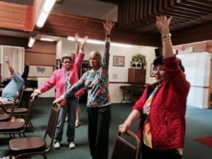 Low vision support group members doing chair yoga led by Mina Izadsepas.
